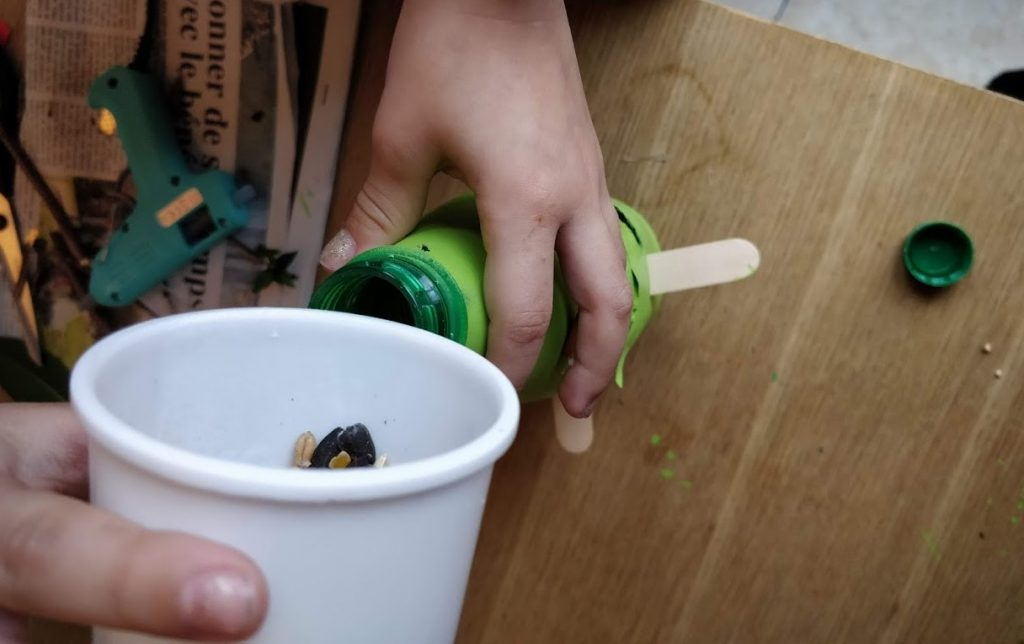 Easy DIY Bird Feeders from recycled materials - Step 5 filling the bird feeder with bird seeds